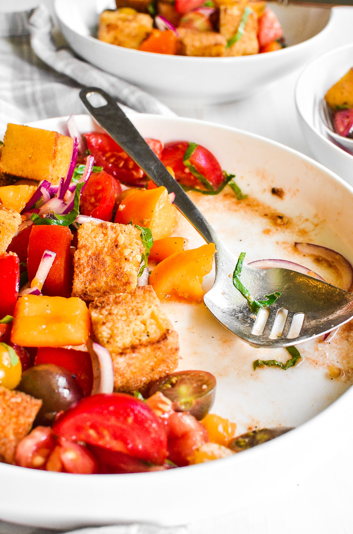 Close up side view of a white platter of cornbread panzanella with a stainless steel serving spoon.