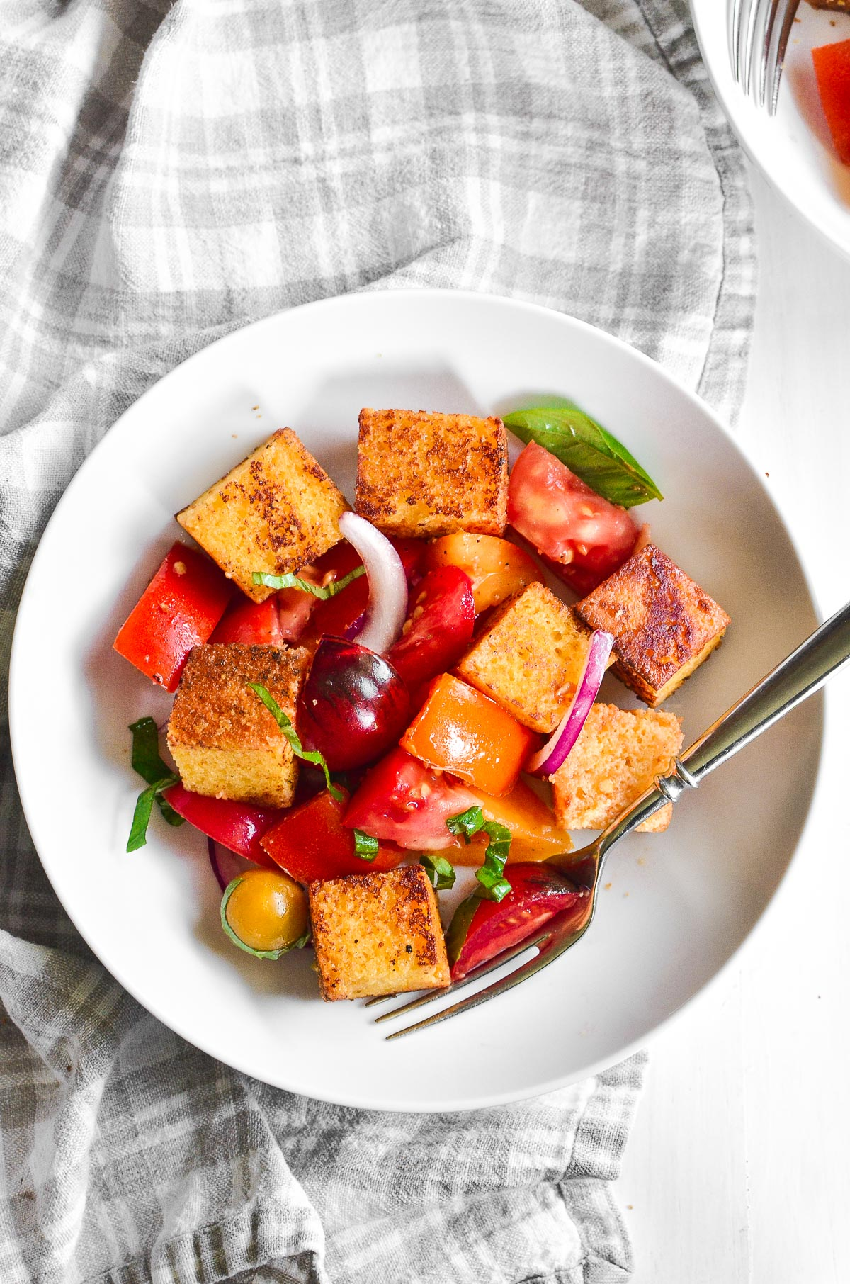A bowl of cornbread panzanella with a fork on a plaid linen towel.