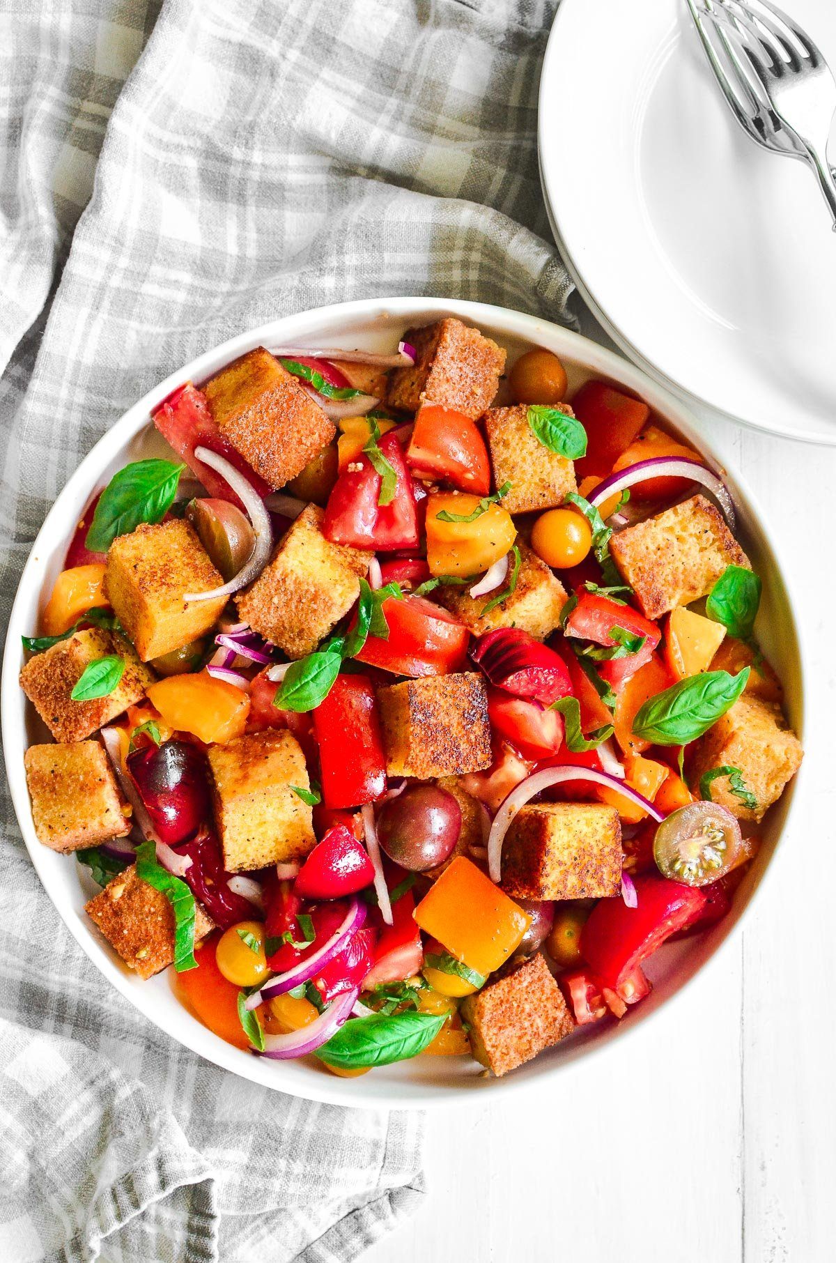 A plate of cornbread panzanella on a white surface with a plaid linen towel and white bowls and forks.