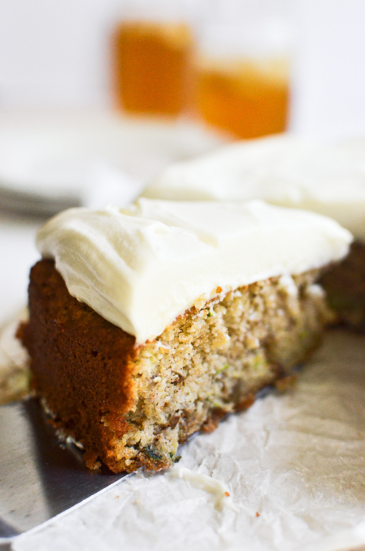 A slice of zucchini cake being pulled out with a cake server.
