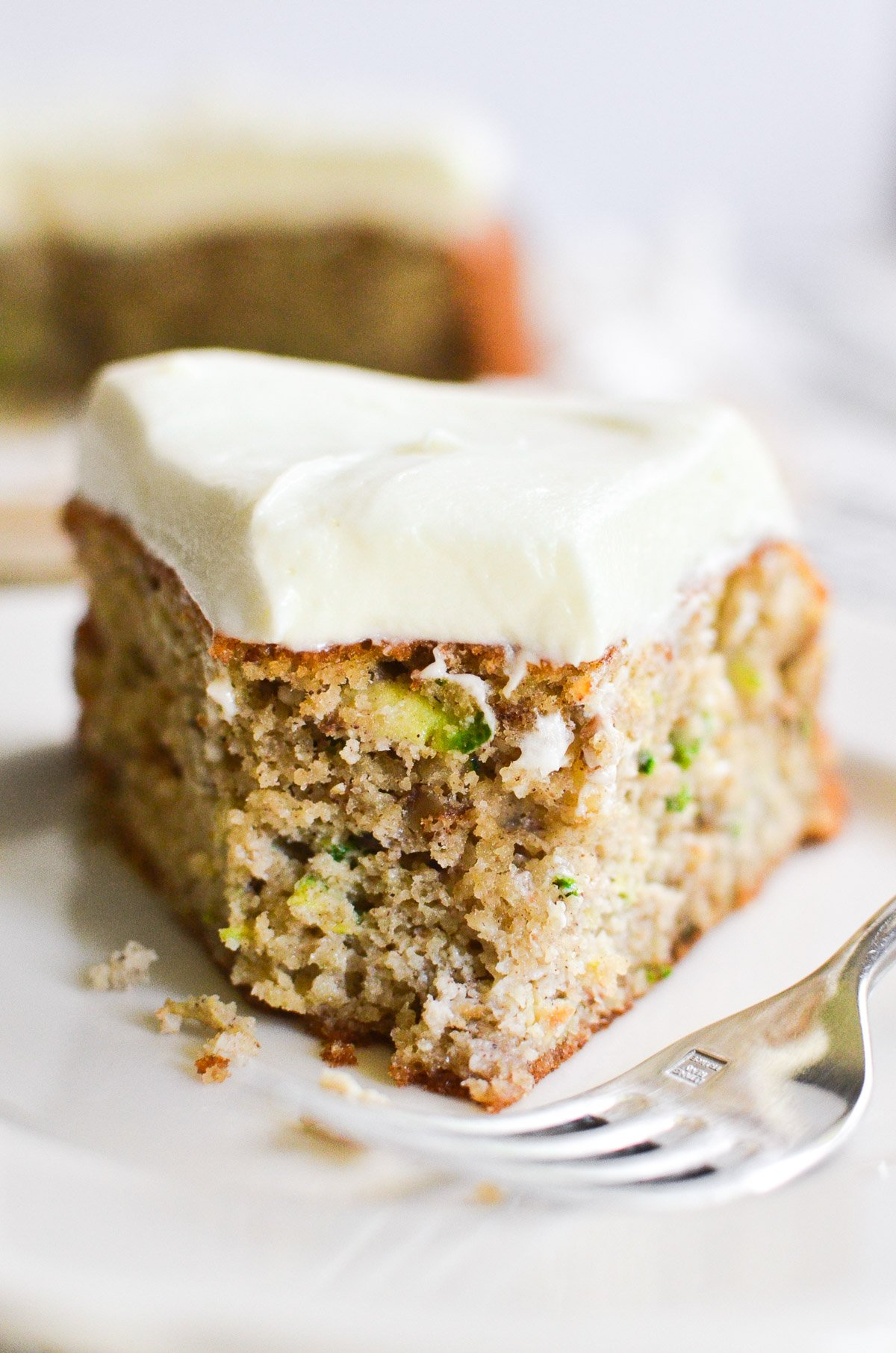A slice of gluten free zucchini cake with a bite taken out of it and a fork on a white plate.