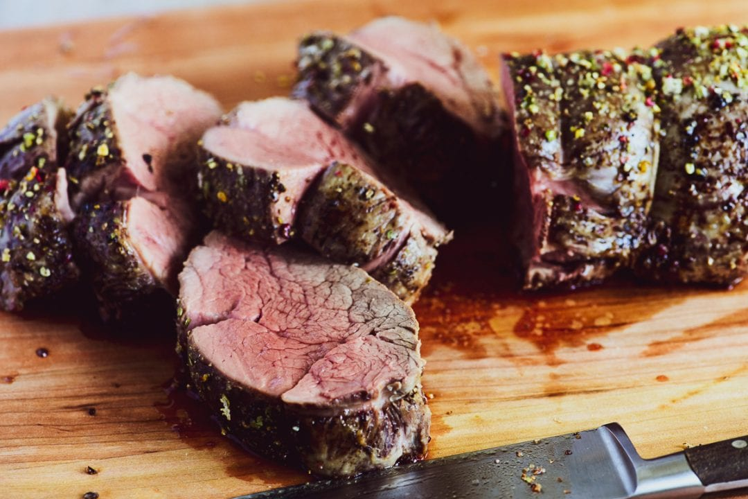 slicing beef tenderloin on a cutting board
