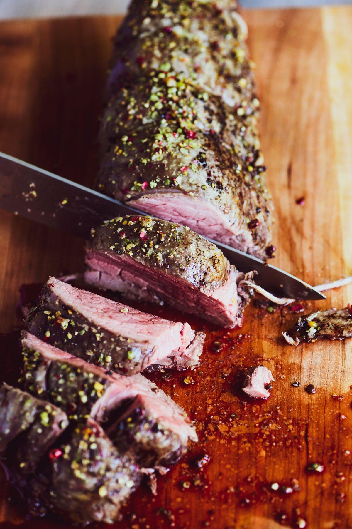beef tenderloin being sliced on a Boos cutting board