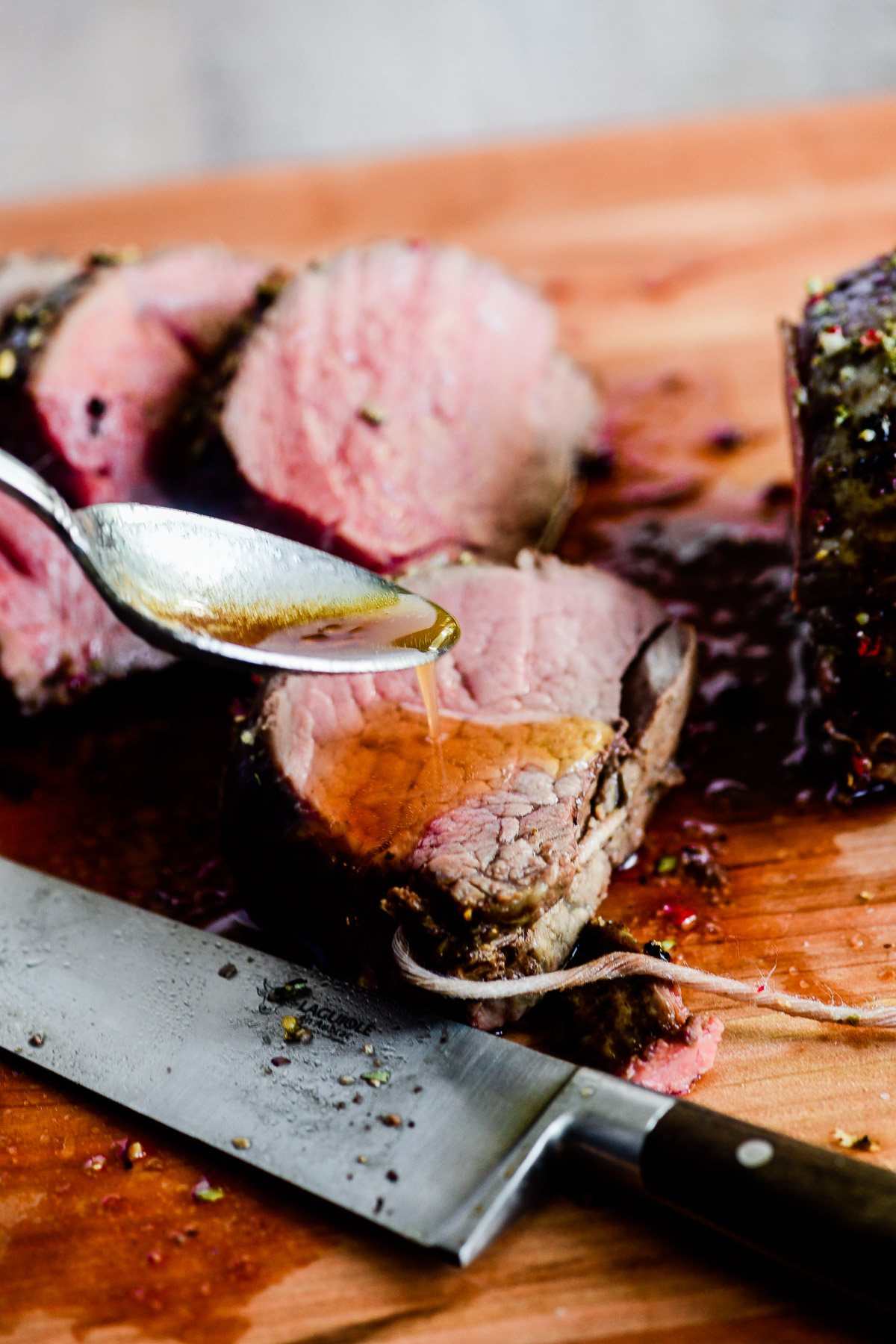 spooning garlic browned butter sauce on steak