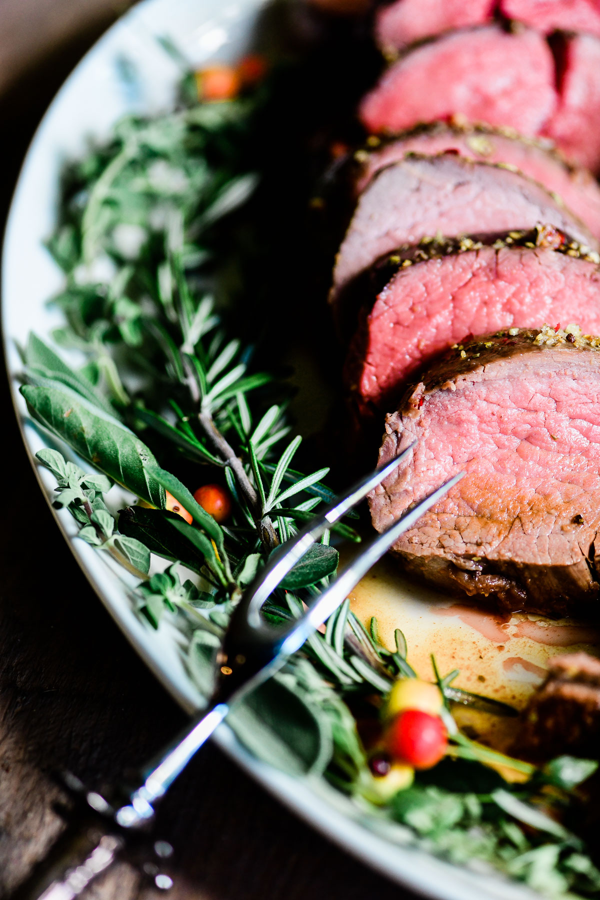 slices of beef tenderloin on a platter with fresh herbs