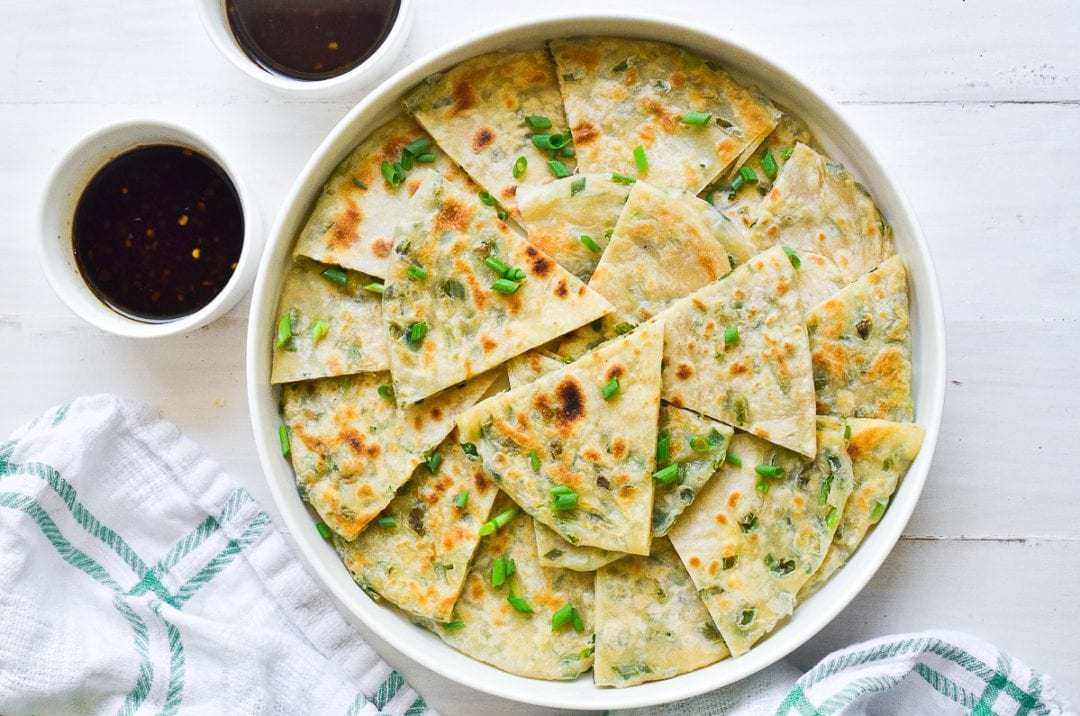 scallion pancakes cut in triangles in a white bowl