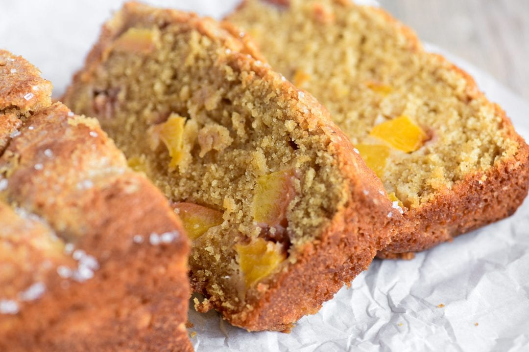 spiced peach bread, sliced on parchment paper