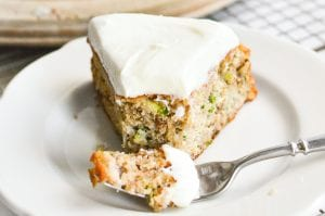 A slice of zucchini cake on a plate with a fork taking a bite.