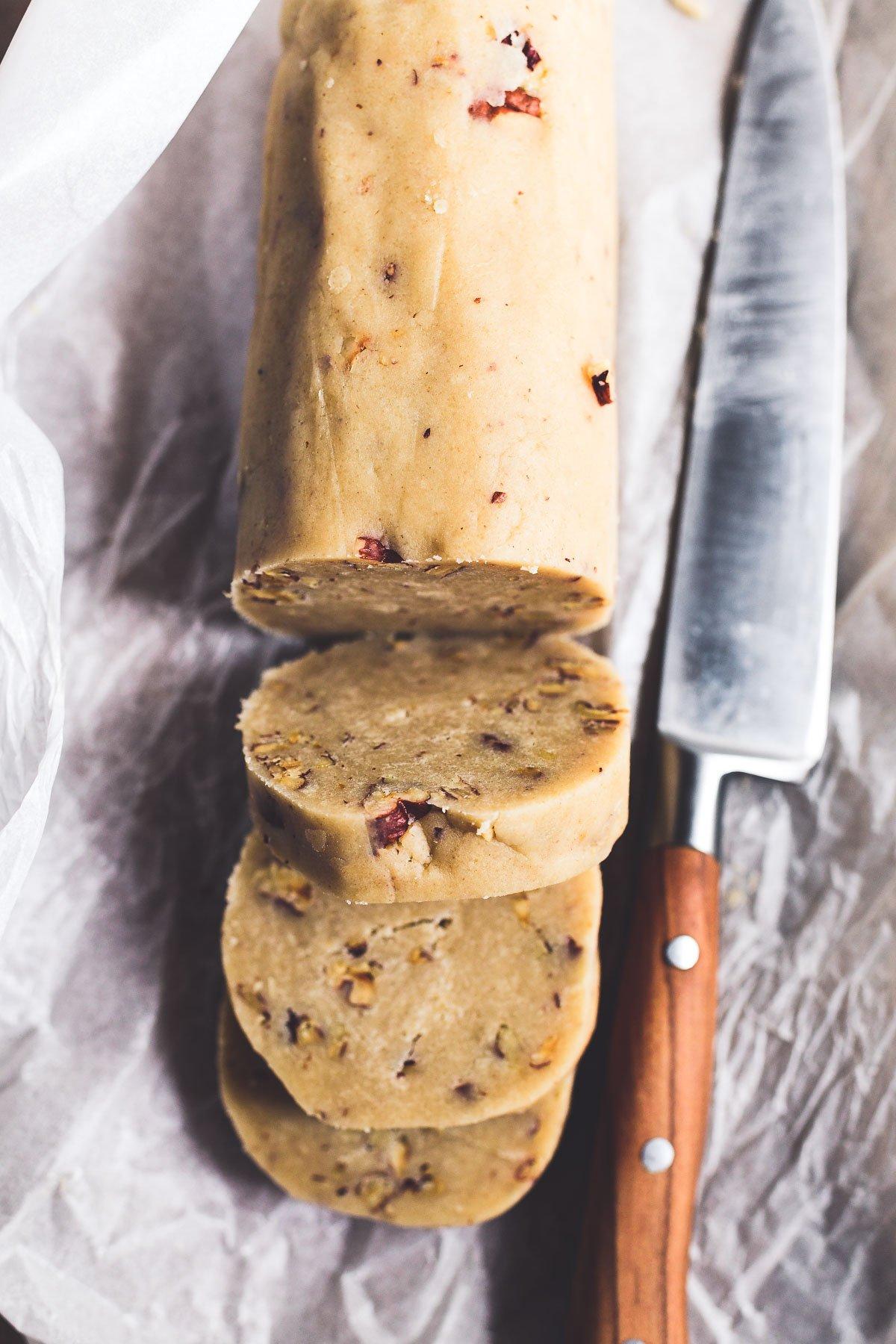 slicing a log of pecan sandies cookie dough
