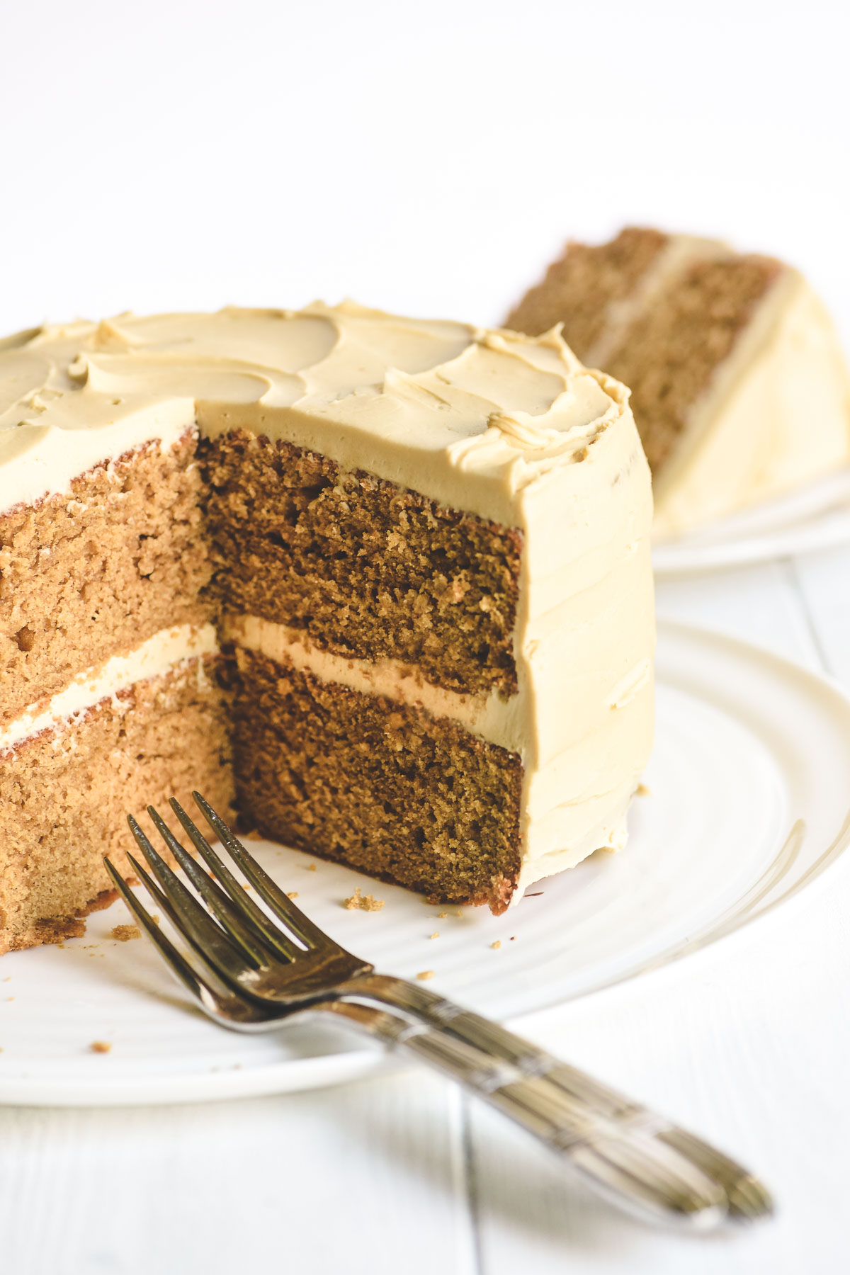 apple butter cake with brown sugar frosting, sliced open on a platter