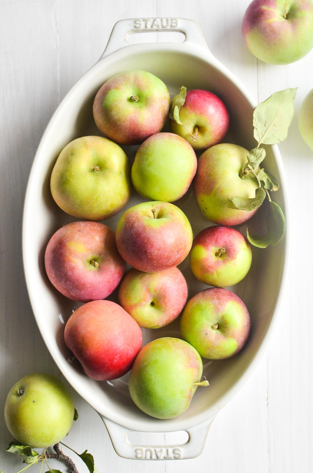 A white oval baking dish filled with apples on a white wooden surface.
