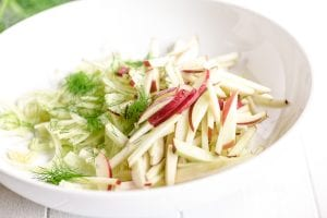 apples and fennel in a white bowl