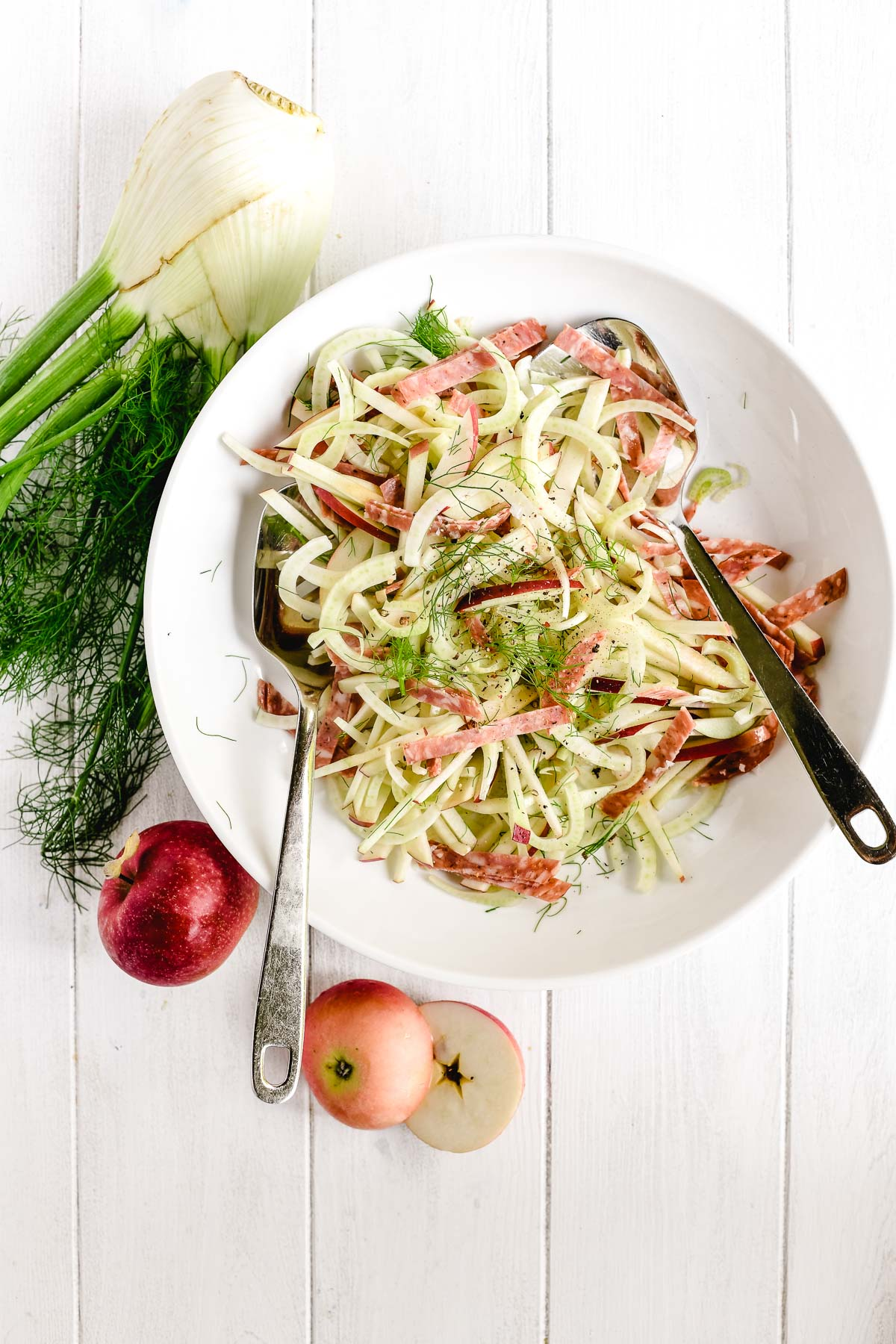 apple, fennel, and salami salad in a white bowl