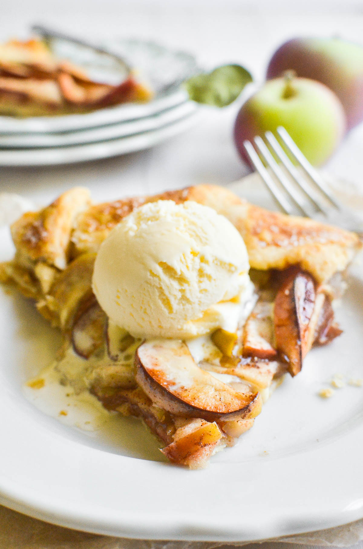 A slice of apple galette topped with a scoop of vanilla ice cream.