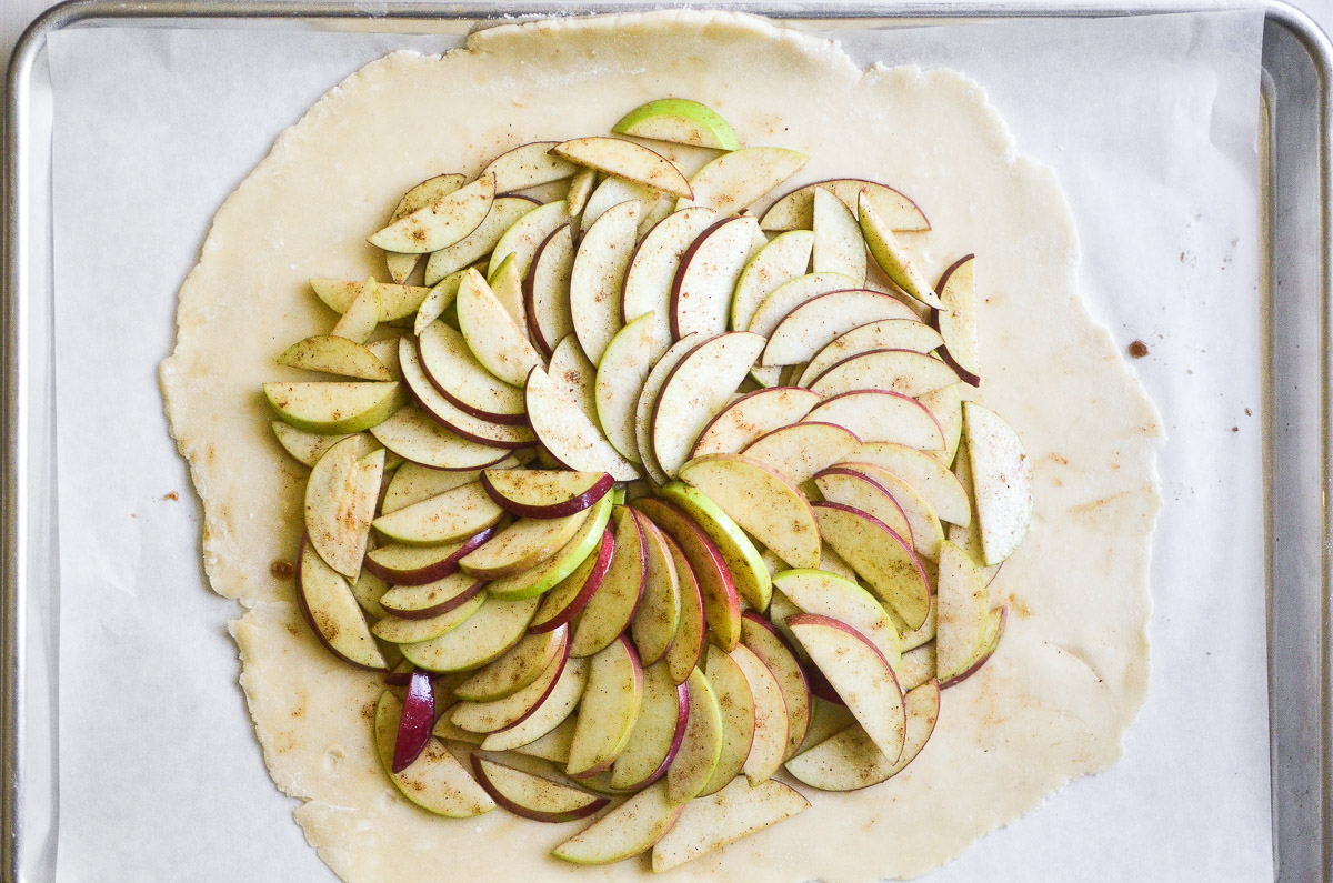 sliced apples on dough for an apple galette