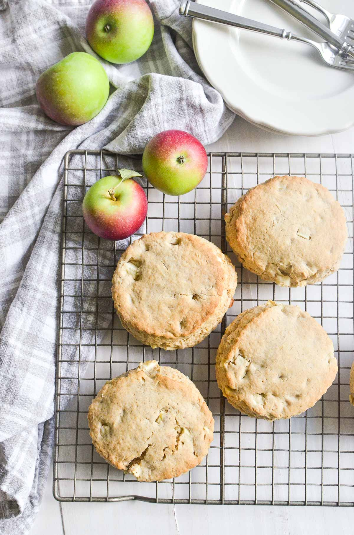 apple scones on a cooling rack with fresh apples