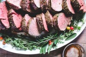 roast beef tenderloin on a platter with herbs