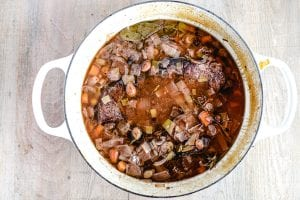 Sauerbraten cooking in a white cast iron pot