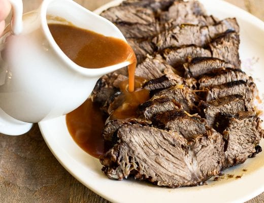 pouring gravy on sliced sauerbraten pot roast