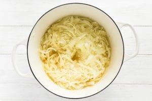 Sliced onions sautéing in a pot