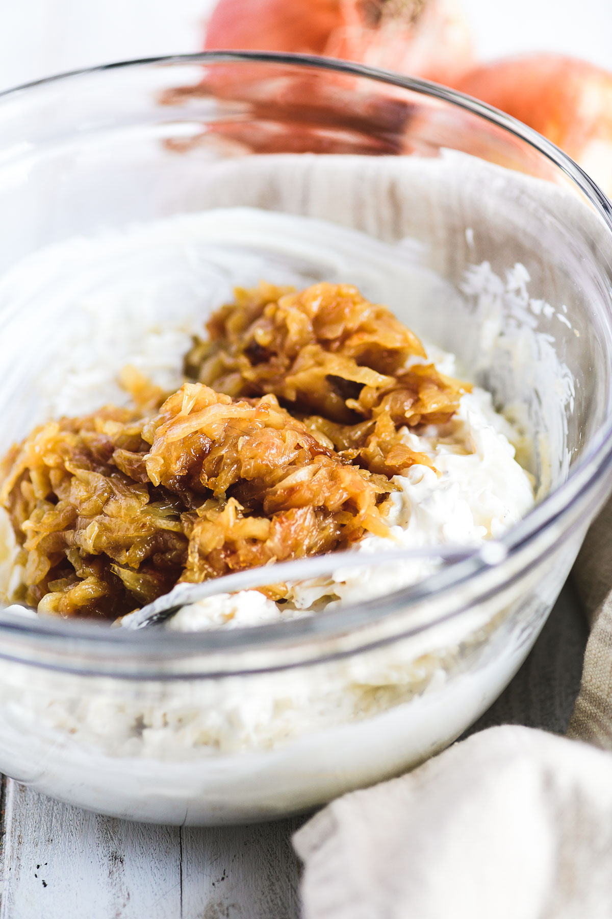 mixing up caramelized onion dip in a bowl