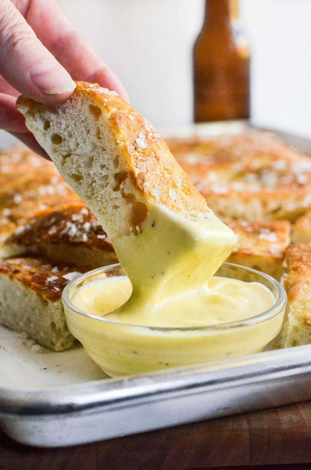 dipping pretzel bread into dipping sauce