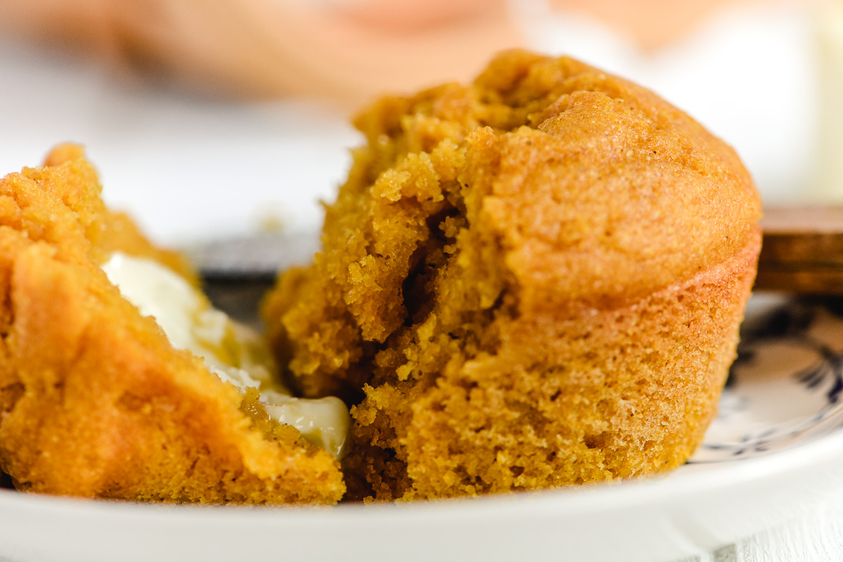 Pumpkin corn muffin on a plate with butter
