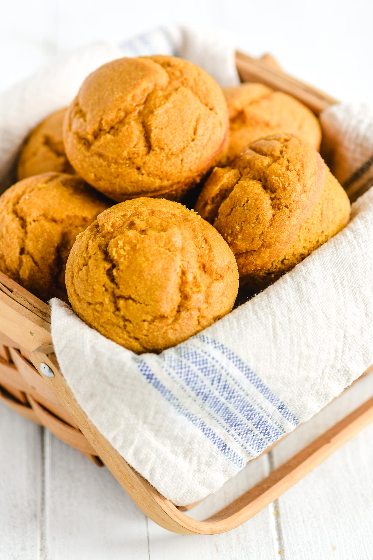 pumpkin cornbread muffins in a basket with napkin