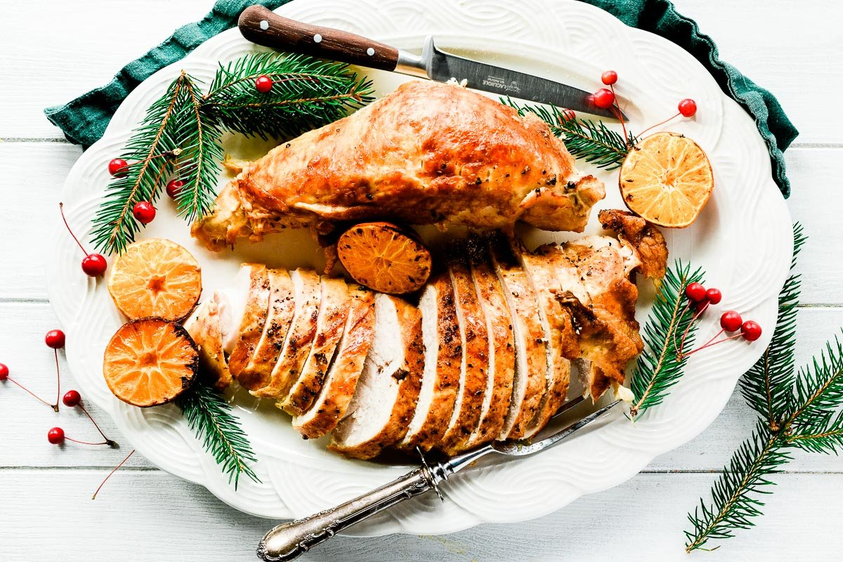 Roasted turkey breast on a platter with clementines, and crab apples