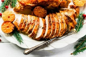 a sliced turkey breast on a platter with clementines