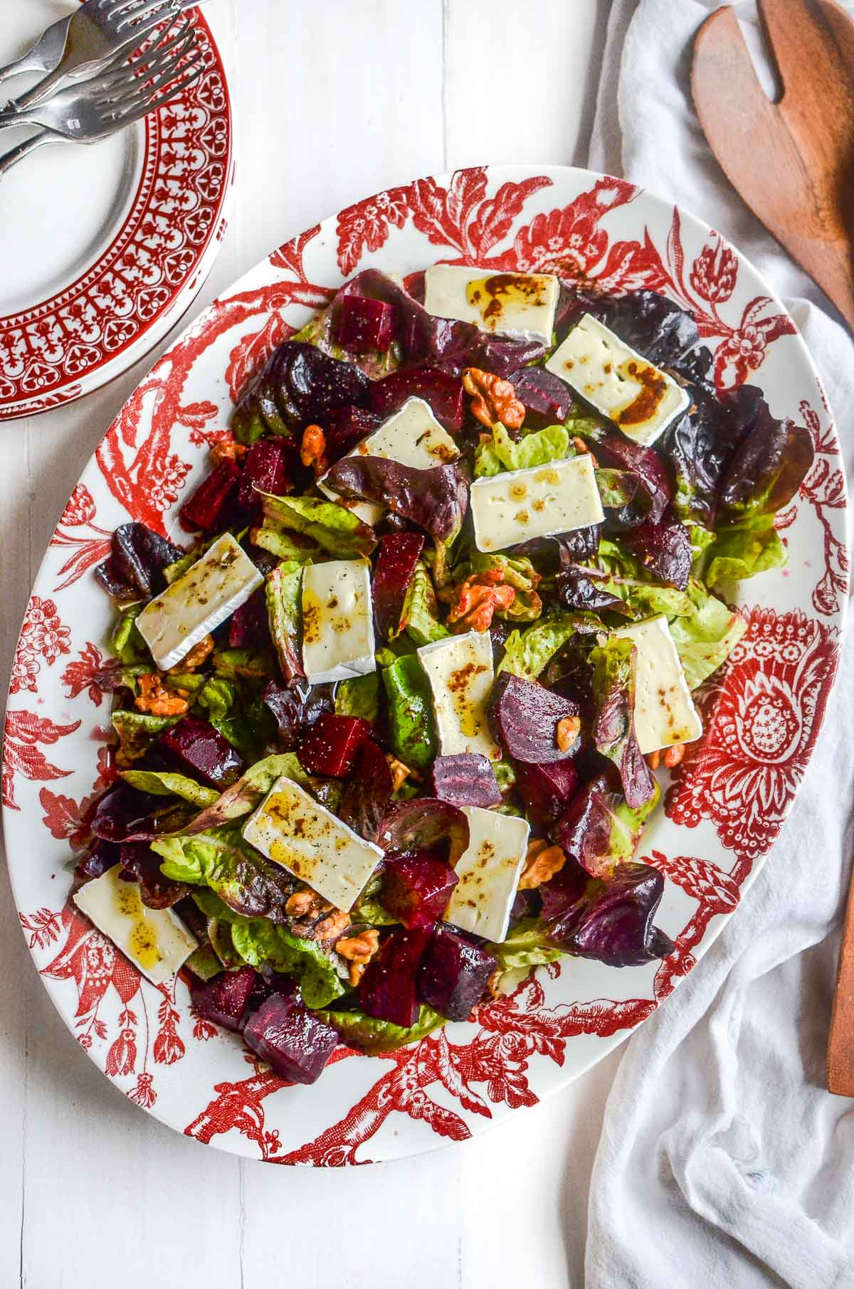 A red patterned platter of roasted beet and brie salad on a white wooden surface.