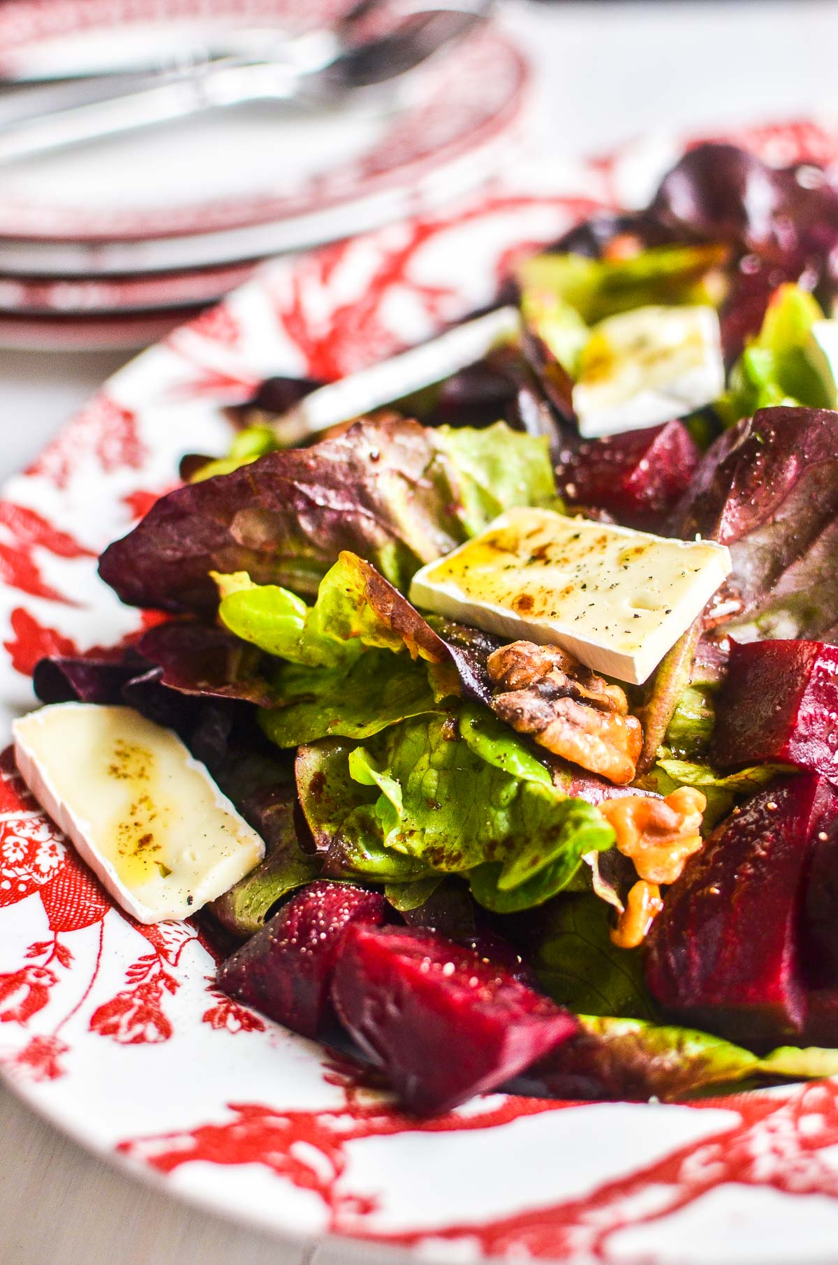 Roasted beet and brie salad on a red patterned platter.