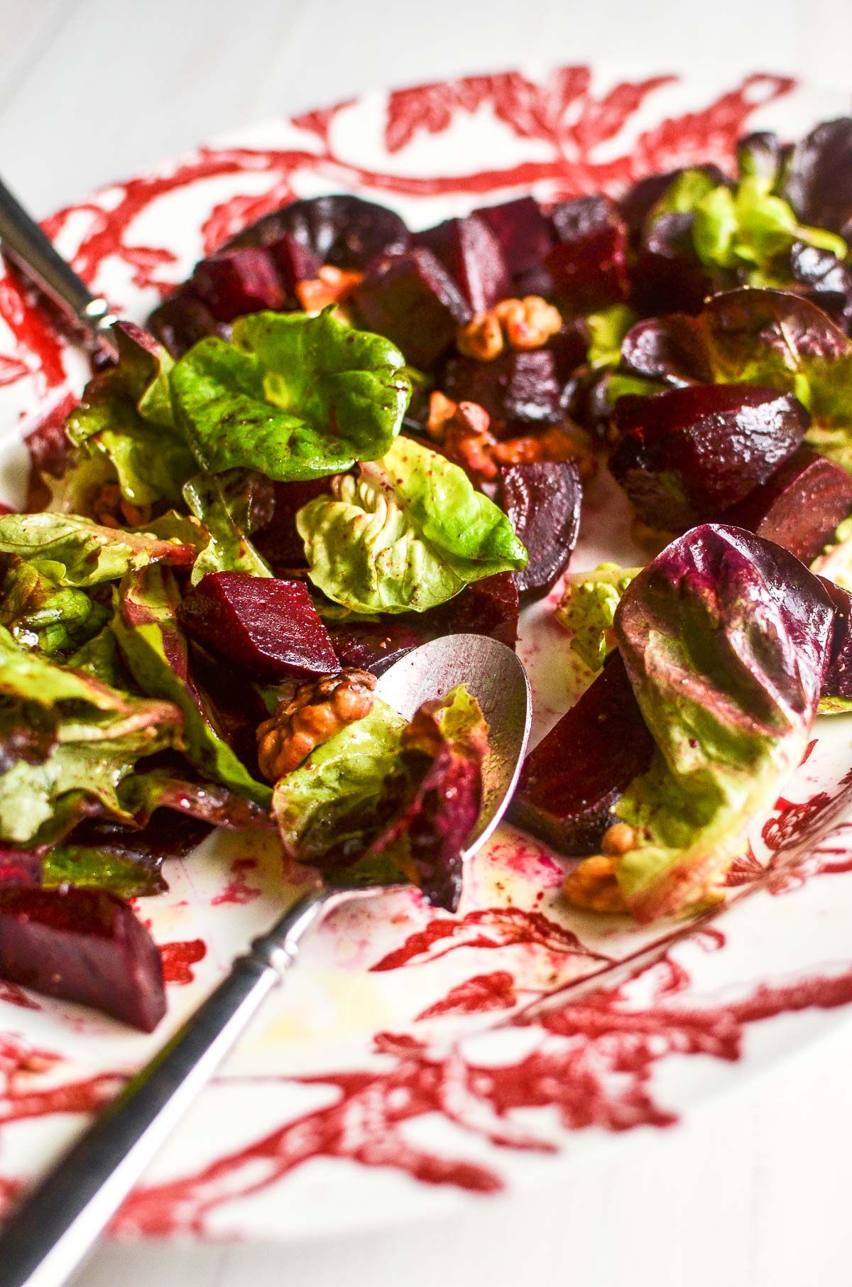 A red patterned platter of roasted beet and brie salad with two serving spoons.