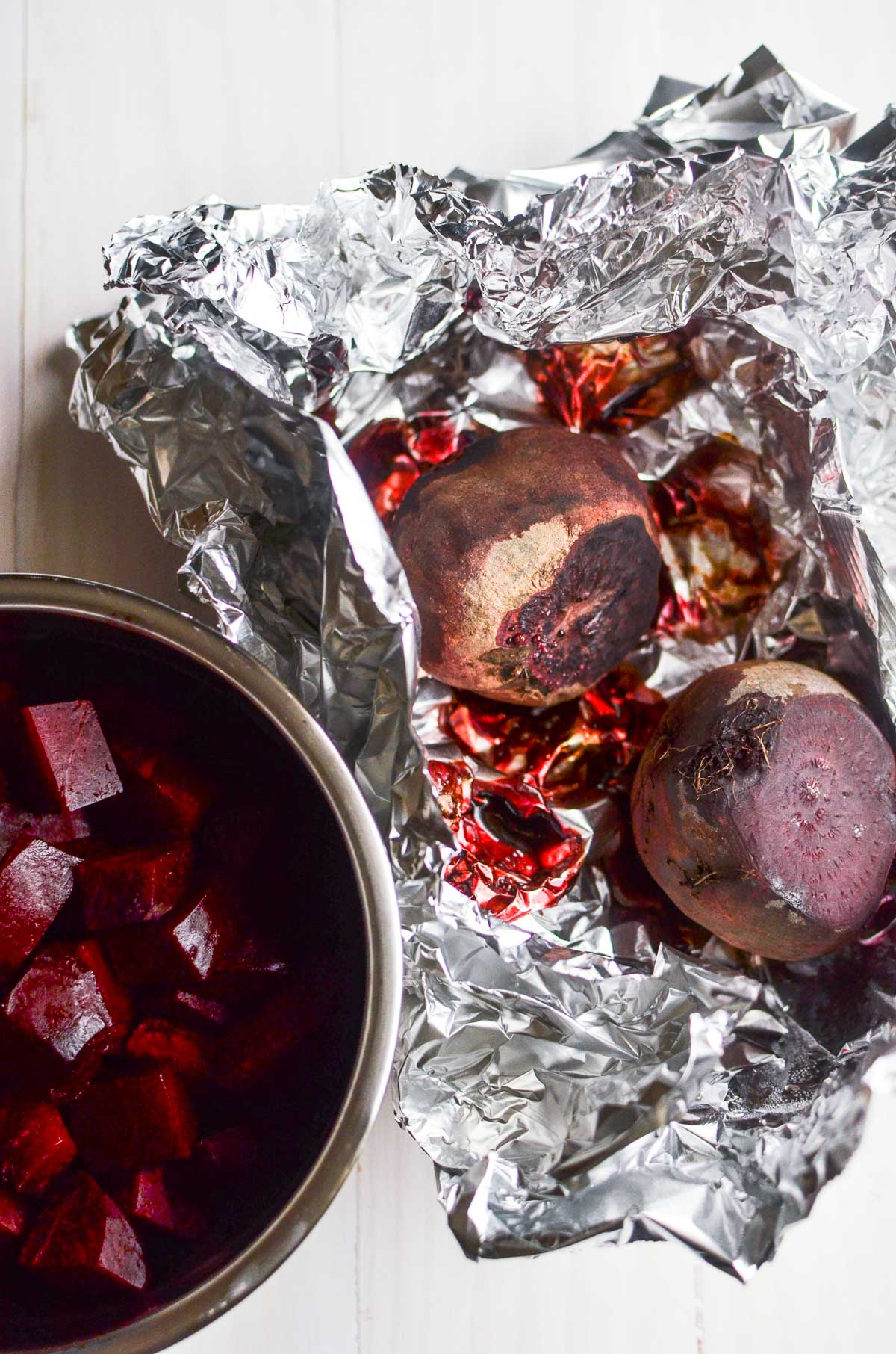 Roasted beets in tinfoil next to a small stainless steel bowl of chopped roasted beets.