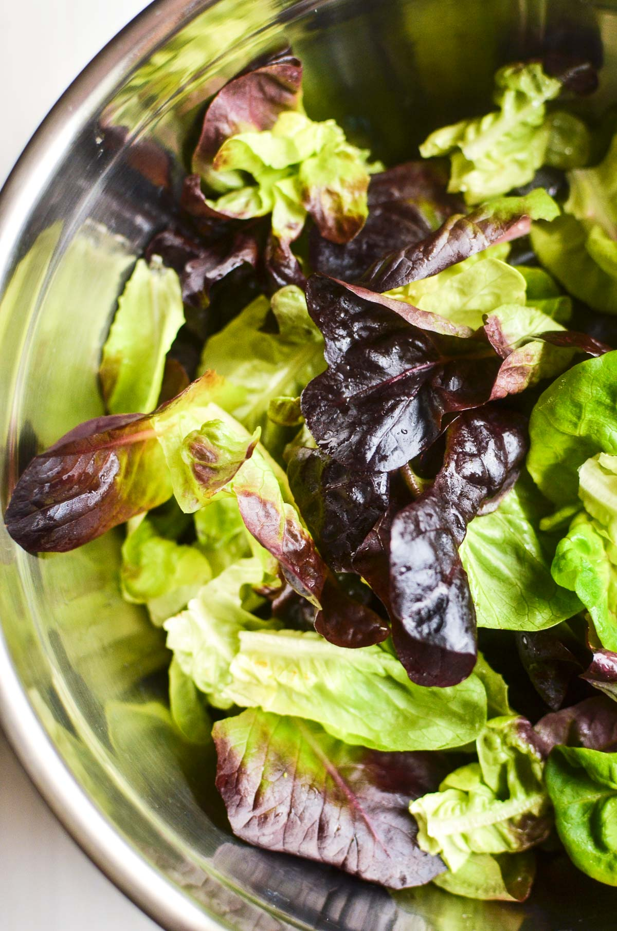 A stainless steel bowl full of fresh salad greens.