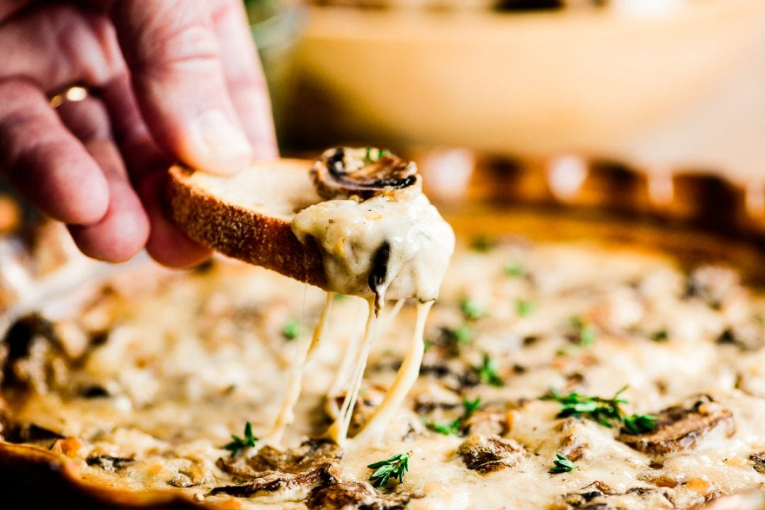 Scooping up baked mushroom dip with toasted bread