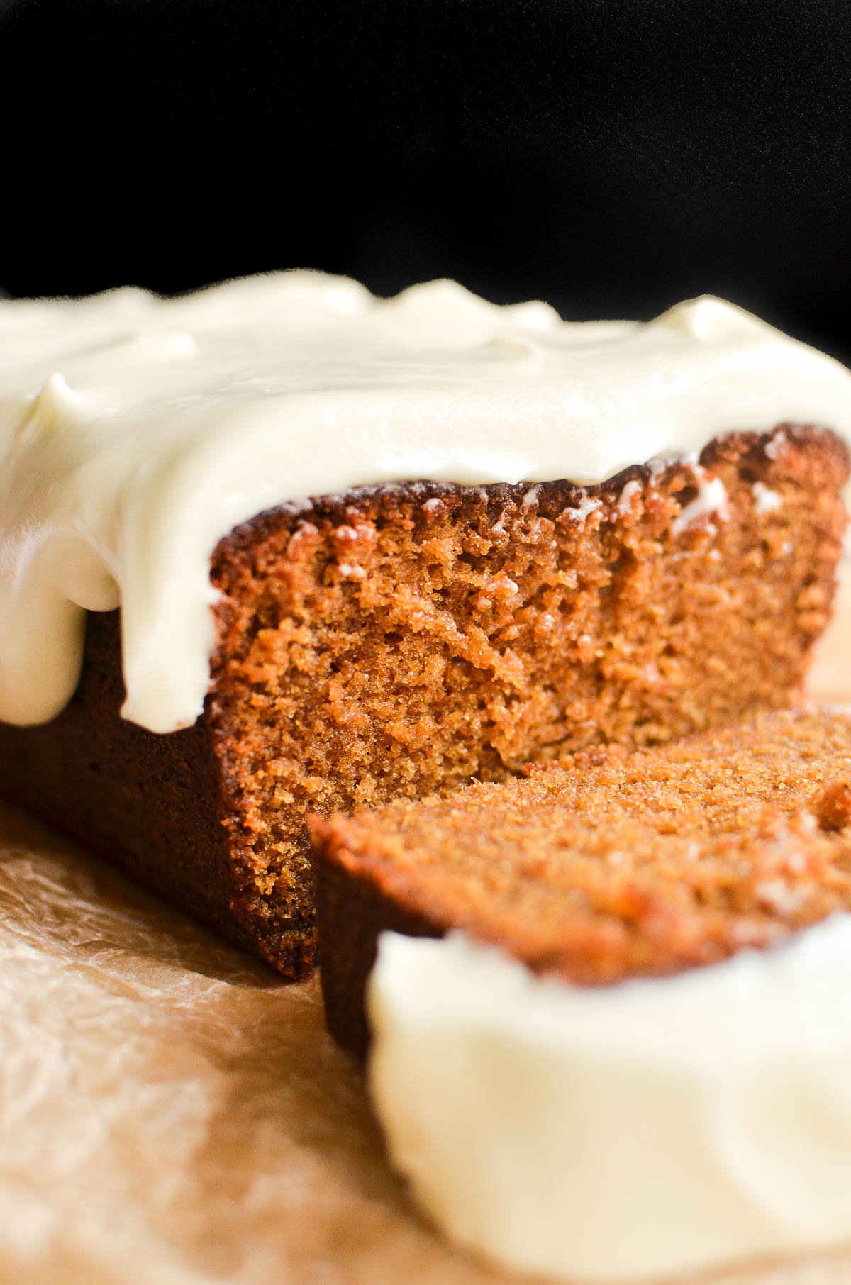 Gingerbread loaf cake sliced, on a piece of parchment paper.