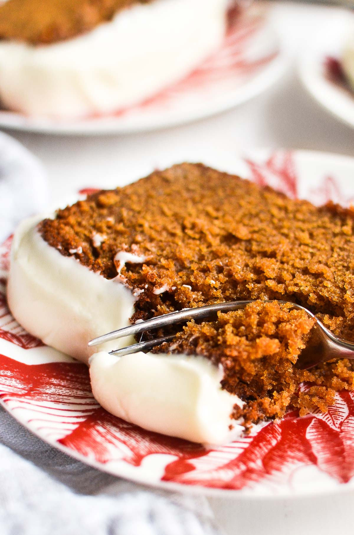 A piece of gingerbread loaf cake with a bite being taken out with a fork.