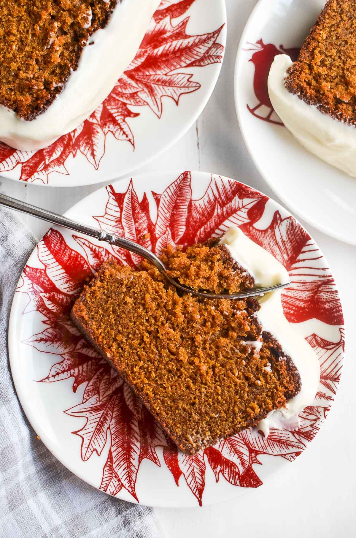Slices of gingerbread loaf cake on red patterned dessert plates on a white surface.