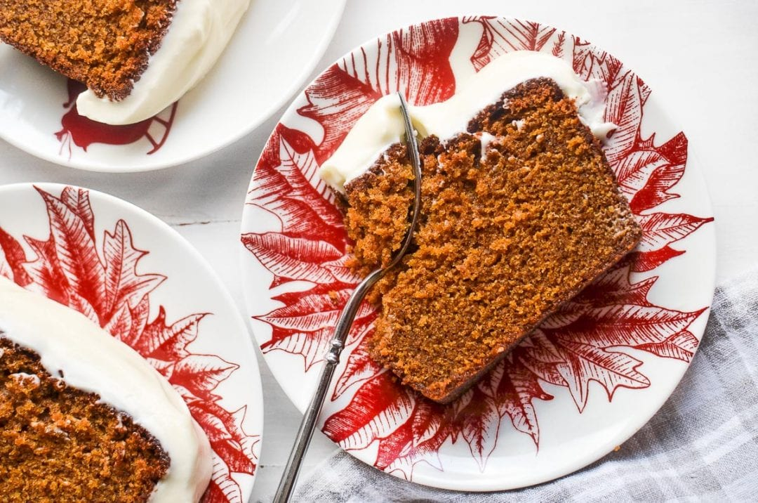 moist gingerbread loaf cake with cream cheese frosting on a plate with fork