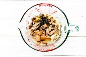 soaking dried mushrooms in chicken stock