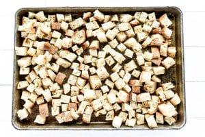 cubed bread toasting on a baking sheet
