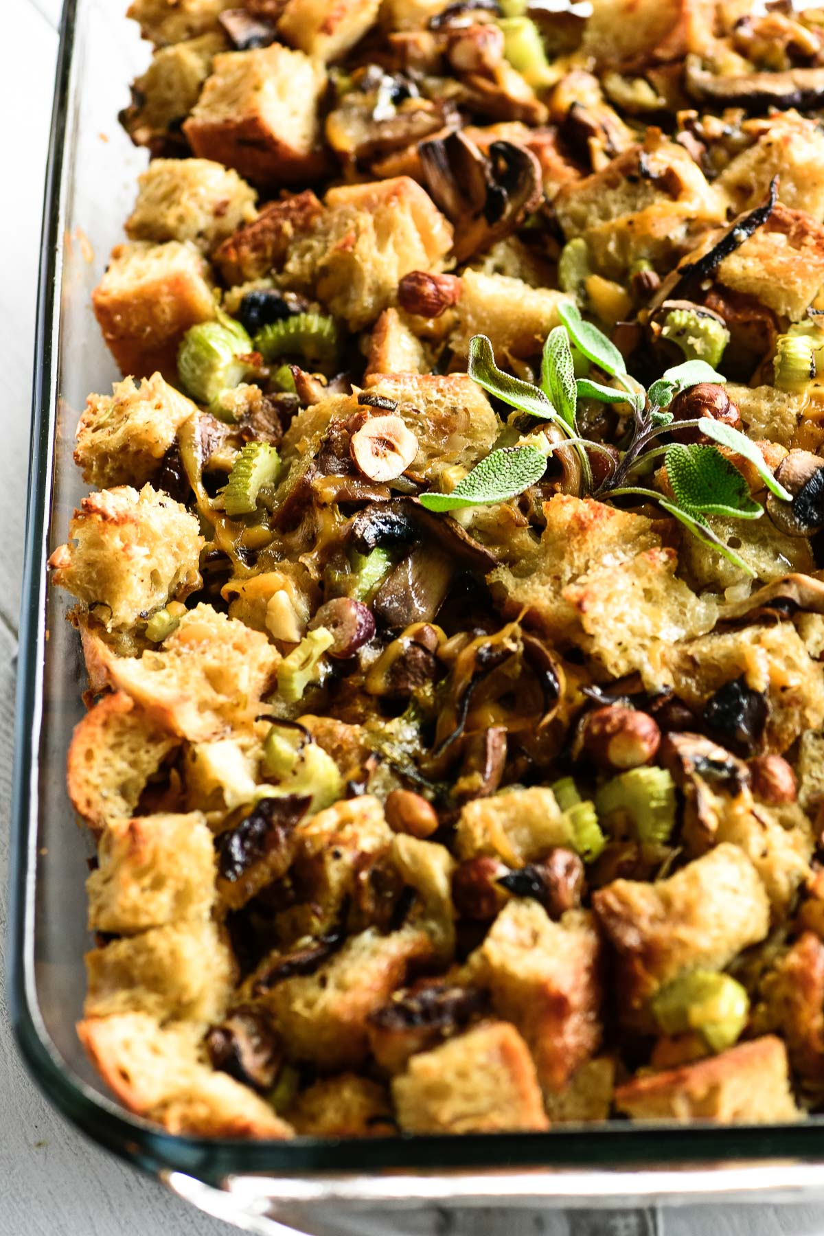 mushroom stuffing with hazelnuts and sage in a glass casserole dish