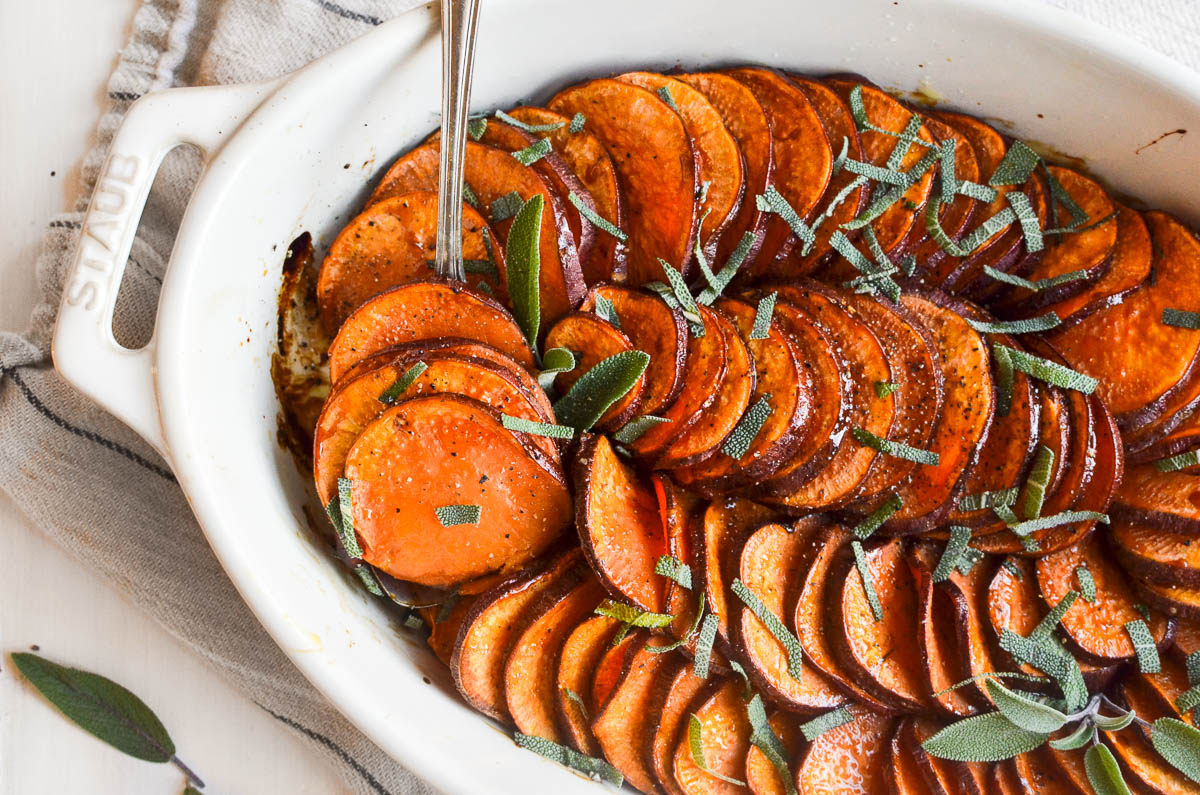 Roasted sweet potatoes in a white ceramic baking dish, garnished with sage leaves.