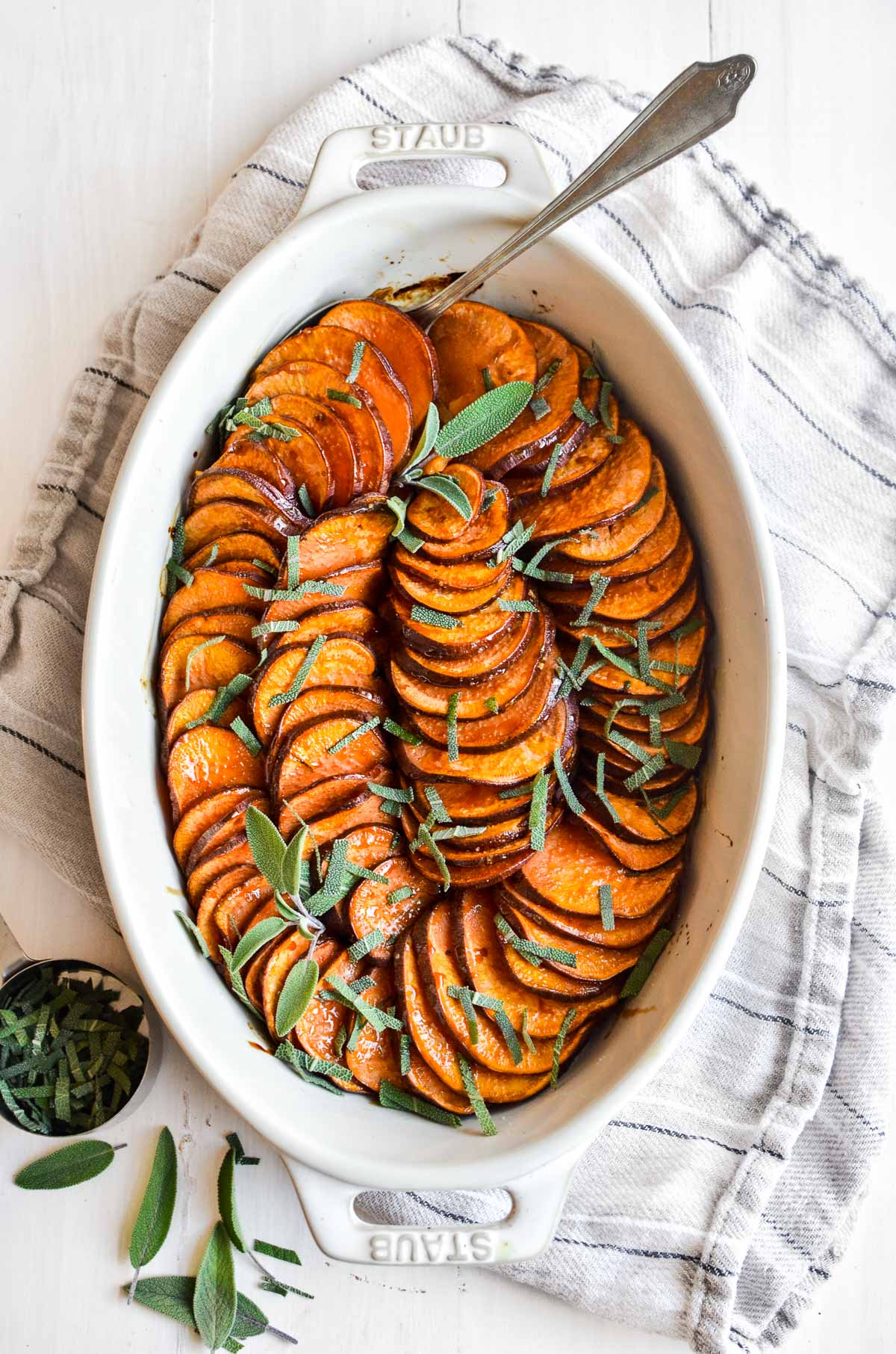 A baking dish of roasted sweet potatoes garnished with sage leaves on a white surface with a striped linen kitchen towel.
