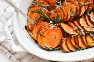 roasted sweet potatoes in a pan with fresh sage