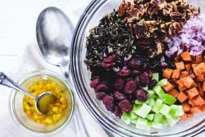 colorful ingredients for a wild rice salad, with maple cider dressing