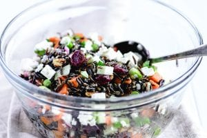 tossing a wild rice salad in a glass bowl