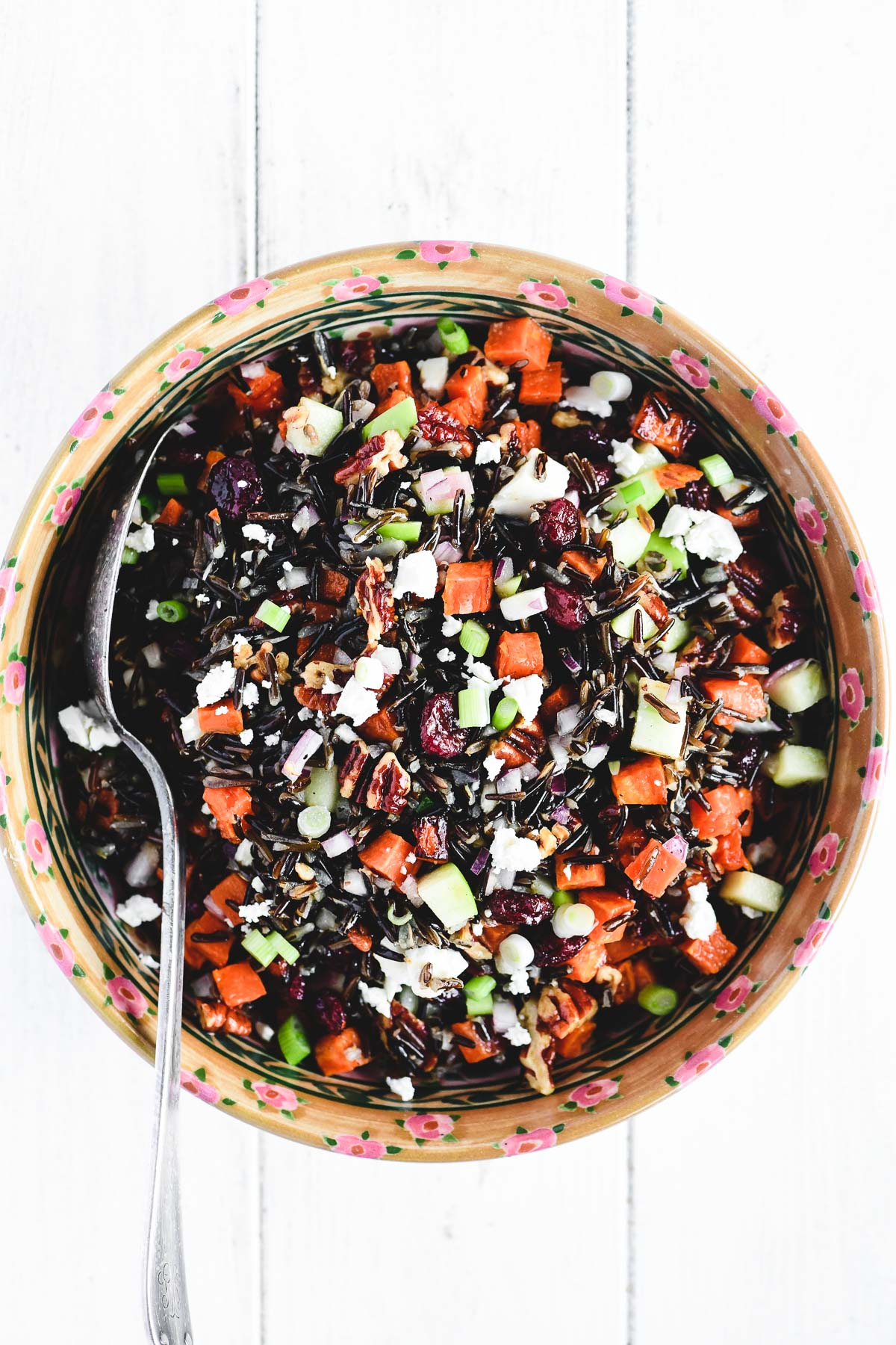 wild rice salad in a serving bowl with spoon
