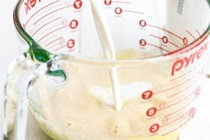 adding milk and cream to egg yolks for eggnog